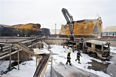 昨日,两位消防员走出古雷石化大火现场。此处油罐被引燃后曾发生多次复燃。新华社发