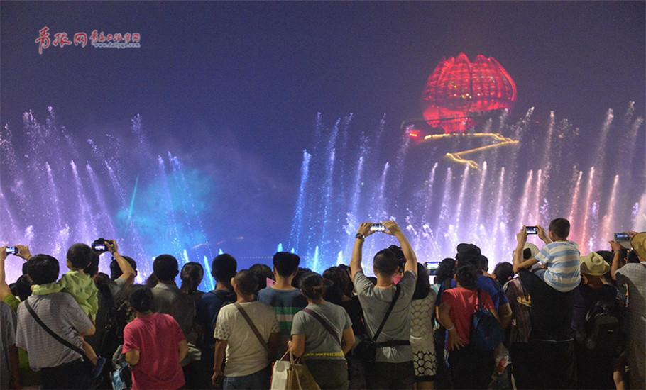入夜的世园会,游人最密集的位置当属天水大坝,人们聚集在此期待着激情澎湃的水舞秀上演。青岛日报记者邢志峰摄影报道。