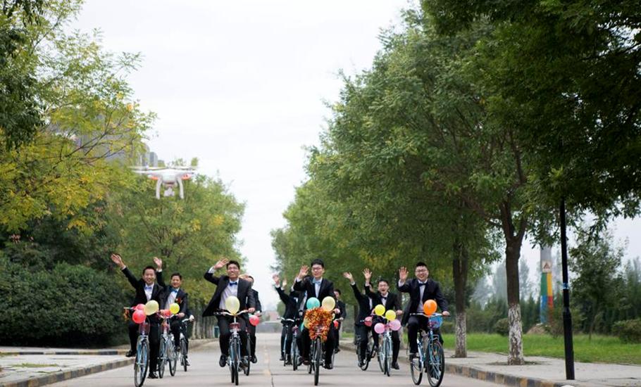 图为西北工业大学16位博士生骑自行车迎女友。