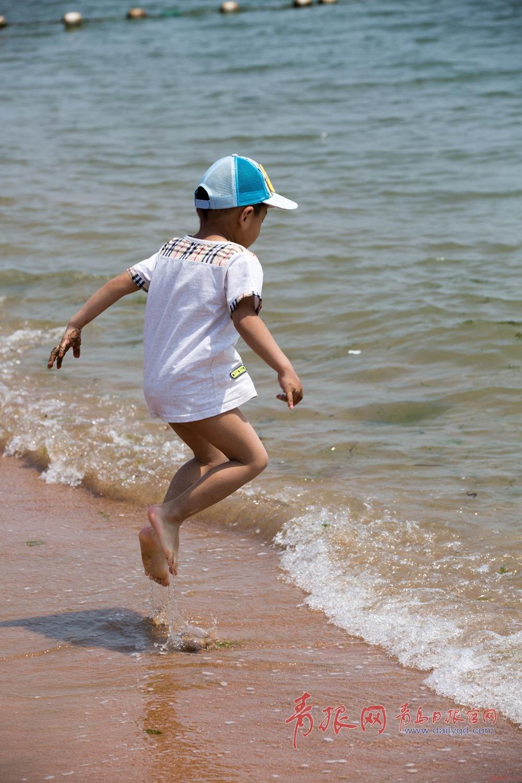 儿童节放假,小孩在海边欢快的跳起来.
