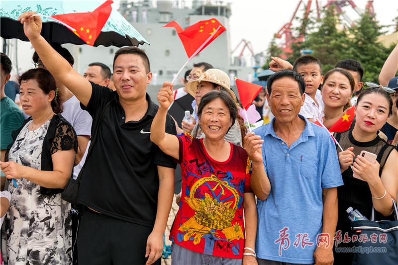 家属手持国旗在码头迎接官兵凯旋。.jpg